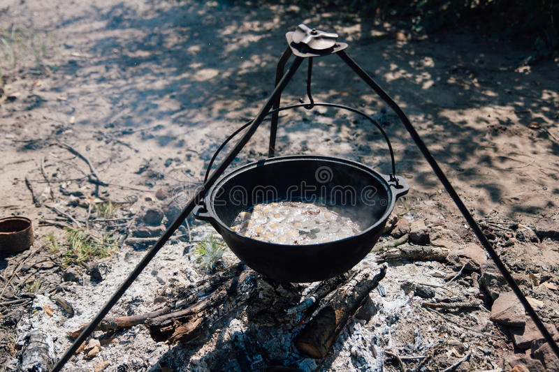 Cast iron pot cooks over open fire in a campsite royalty free stock photography
