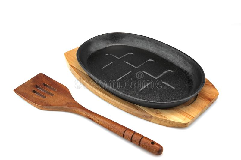 Cast Iron Serving Pan On Wood Plate, Spatula White. New, Clean And Empty Cast Iron Serving Griddles Or Pan With Wood Plate And Wooden Spatula On White Background stock photos
