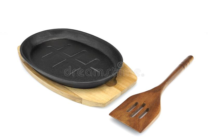 Cast Iron Serving Pan On Wood Plate, Spatula White. New, Clean And Empty Cast Iron Serving Griddles Or Pan With Wood Plate And Wooden Spatula On White Background stock photography