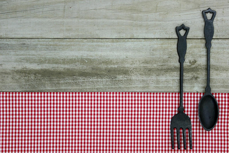 cast iron spoon and fork on red gingham tablecloth with