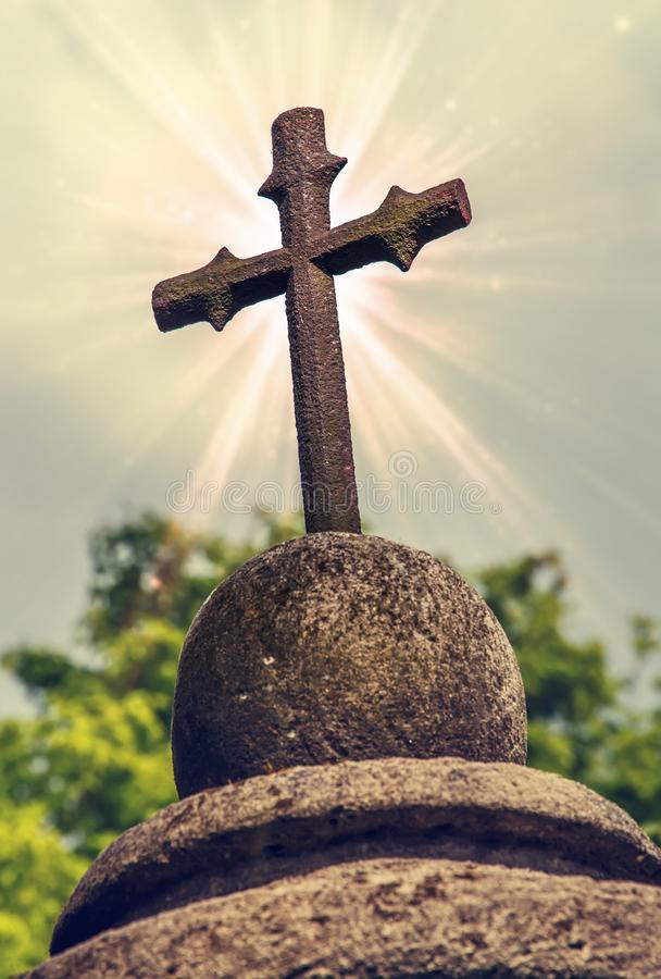 Cast metal cross. element headstone carved from sand stone. old sculpture covered with moss. stock photography