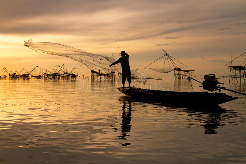 Cast a net. A fisherman is cast a net in the early morning royalty free stock images