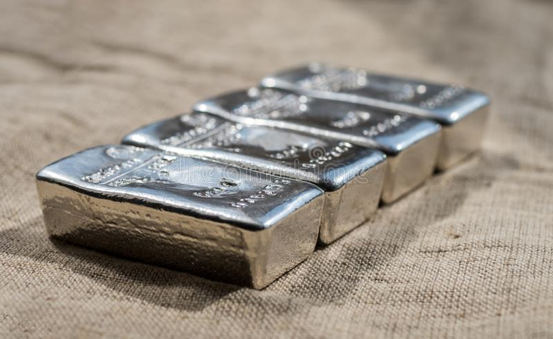 Cast silver bars against the background of the rough texture coarse cloth. Selective focus.  stock photo