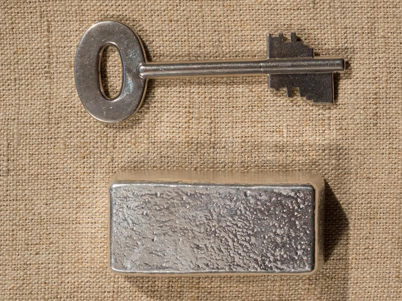 Cast silver bars and the key to the safe against a rough texture of the fabric.  stock photos