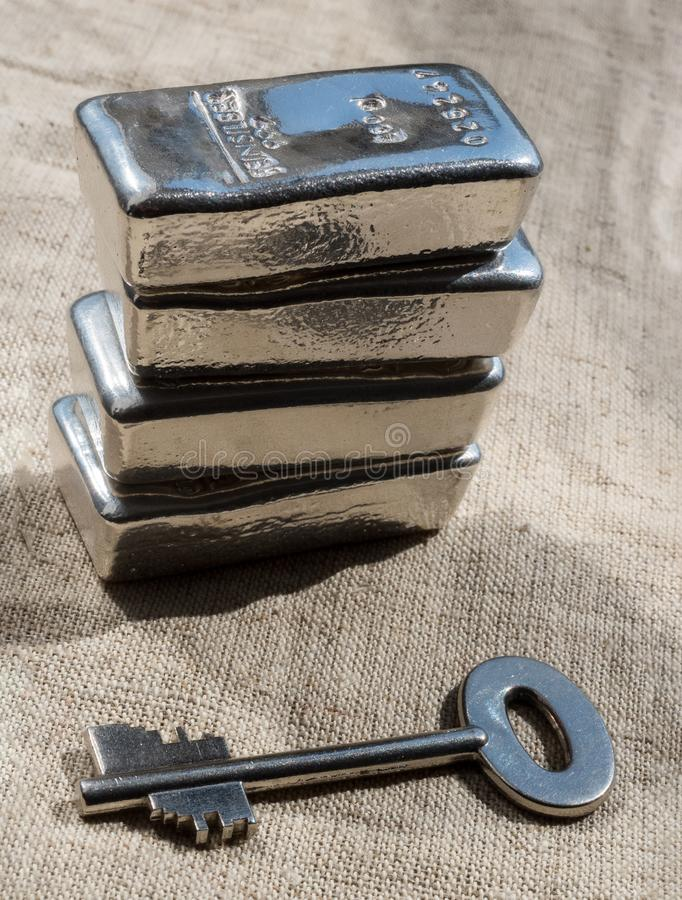 Cast silver bars and the key to the safe against a rough texture of the fabric. Feinsilber is fine silver royalty free stock photography