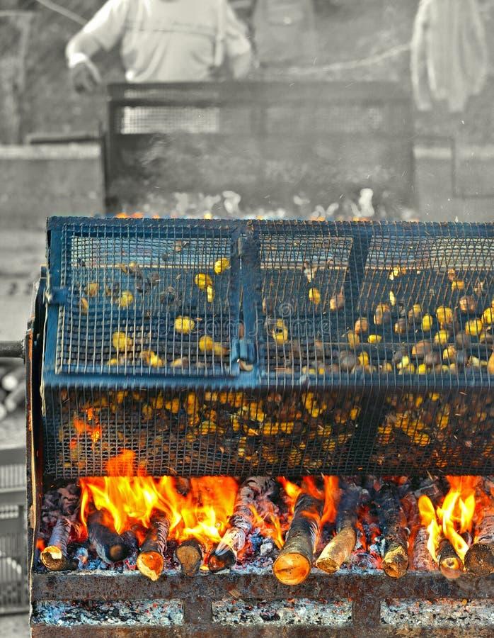 Castañas asadas en jaulas de hierro rodantes viejas sobre el fuego en Sagra justa tradicional en otoño en la pequeña ciudad medie fotos de archivo