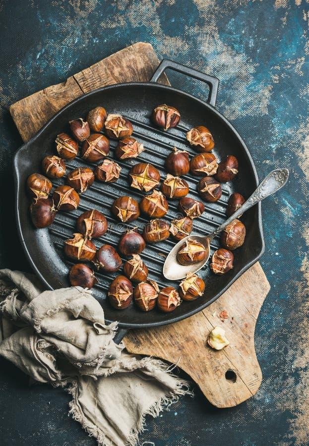 Castagne arrostite nel grigliare pentola sopra fondo blu scuro immagini stock