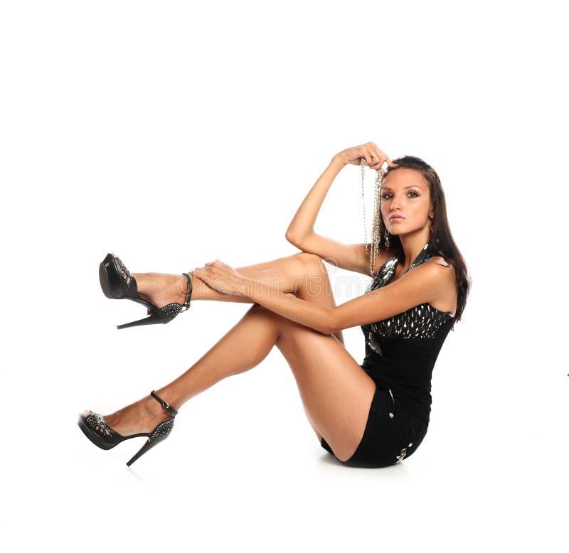 Castana abbronzato attraente in biancheria intima nera si siede sul pavimento, il colpo pieno del corpo, colpo dello studio immagini stock