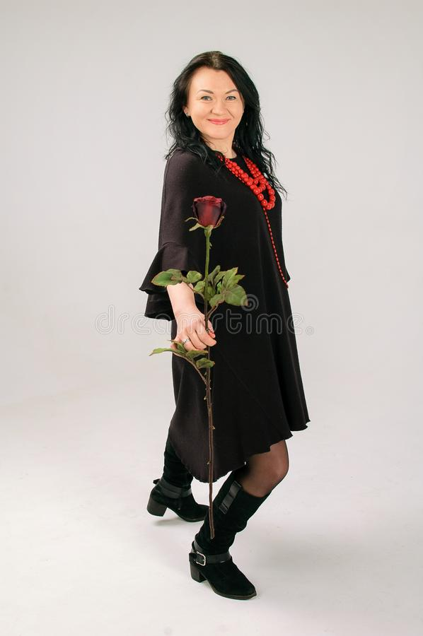 Castana adorabile in un vestito nero Gli sbattimenti della gonna In sua mano, una donna tiene una rosa rossa, lei ha perle rosse  fotografia stock libera da diritti