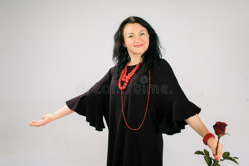 Castana adorabile in un vestito nero Gli sbattimenti della gonna In sua mano, una donna tiene una rosa rossa, lei ha perle rosse  immagine stock