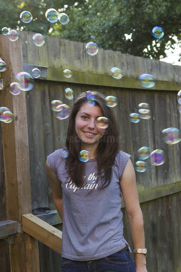 Castana affascinante con le bolle all'aperto fotografie stock
