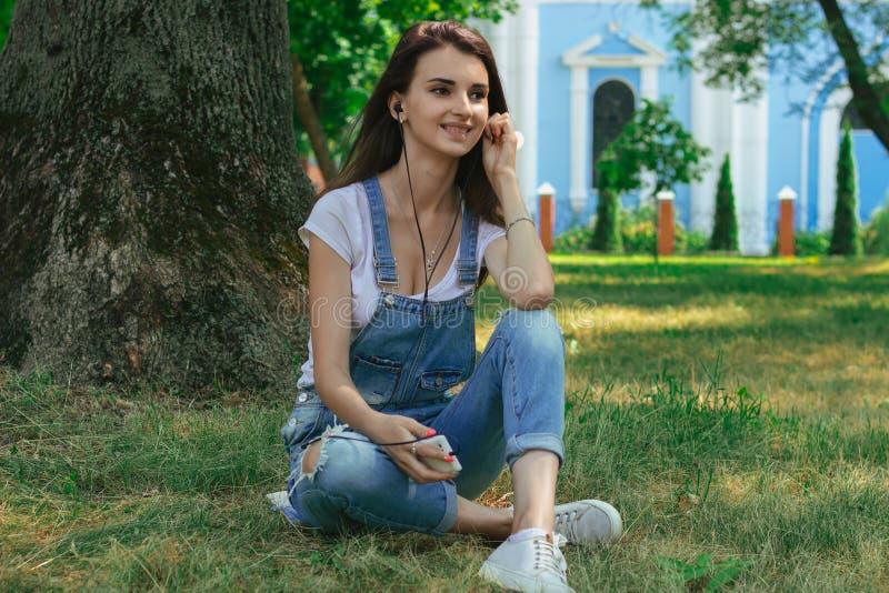 Castana allegro si siede sull'erba e sull'ascoltare la musica fotografia stock libera da diritti