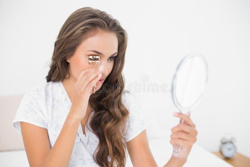 Castana attraente contento facendo uso di un bigodino e di uno specchio del ciglio fotografia stock libera da diritti
