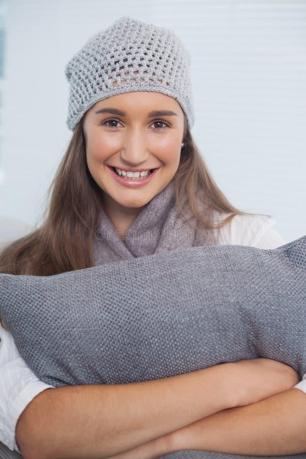 Castana attraente felice con il cappello di inverno sulla posa fotografie stock libere da diritti
