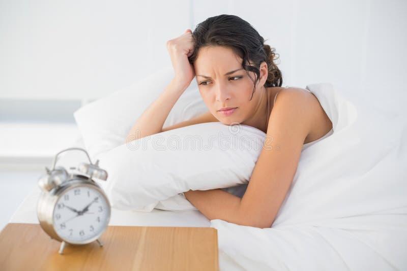 Castana casuale aggrottante le sopracciglia in pigiami bianchi che esaminano la sua sveglia fotografia stock