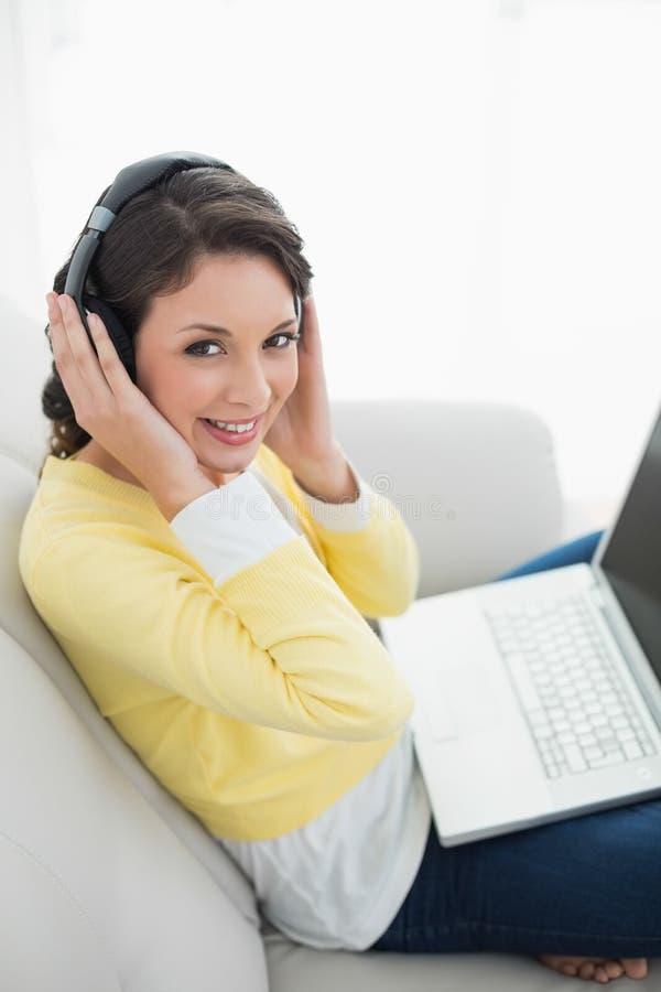 Castana casuale allegro in cardigan giallo che ascolta la musica mentre per mezzo di un computer portatile fotografie stock