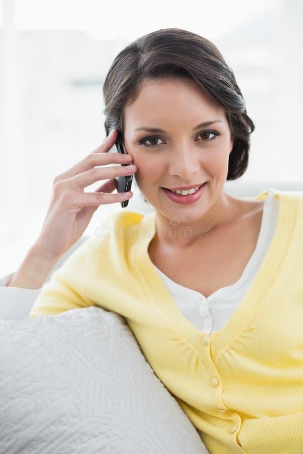 Castana casuale felice in cardigan giallo che chiama con il suo telefono cellulare fotografia stock libera da diritti