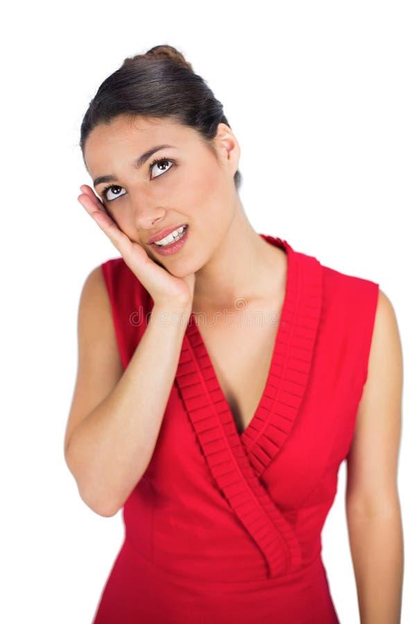 Castana dai capelli legato sexy nel pensiero rosso del vestito fotografia stock