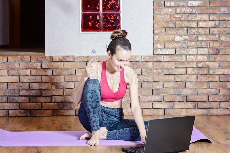 Castana di mezza età attraente prende una rottura dagli esercizi mentre si siede su una stuoia della palestra, acqua potabile ed  fotografia stock