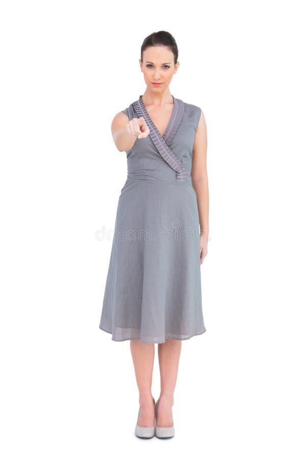 Castana elegante serio in vestito di classe che indica alla macchina fotografica fotografia stock