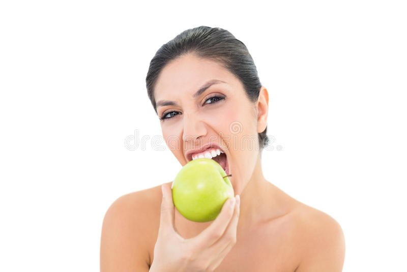 Castana felice mangiando una mela verde ed esaminando macchina fotografica fotografia stock libera da diritti