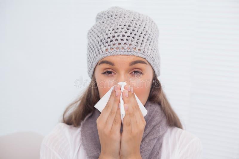 Castana malato con il cappello di inverno sul salto del suo naso immagine stock