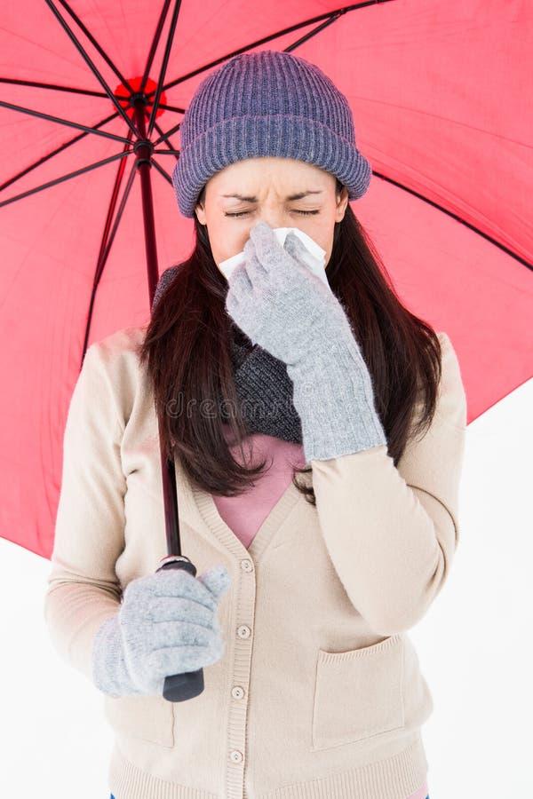 Castana malato soffiando il suo naso mentre tenendo un ombrello immagine stock libera da diritti