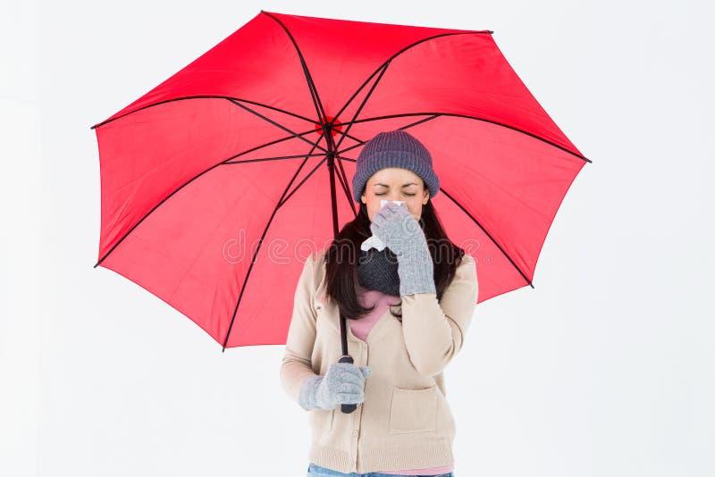 Castana malato soffiando il suo naso mentre tenendo un ombrello immagine stock