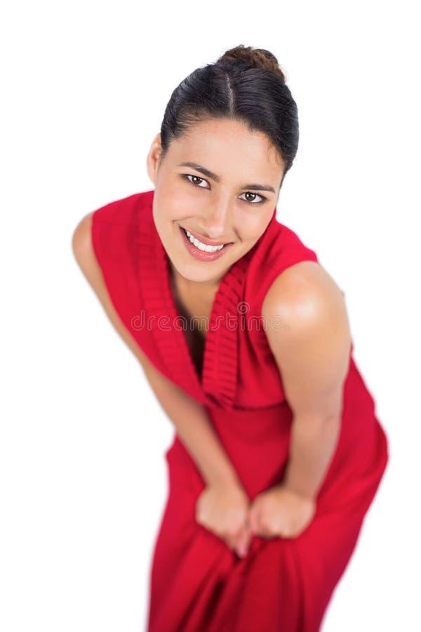 Castana misterioso allegro nella posa rossa del vestito fotografia stock