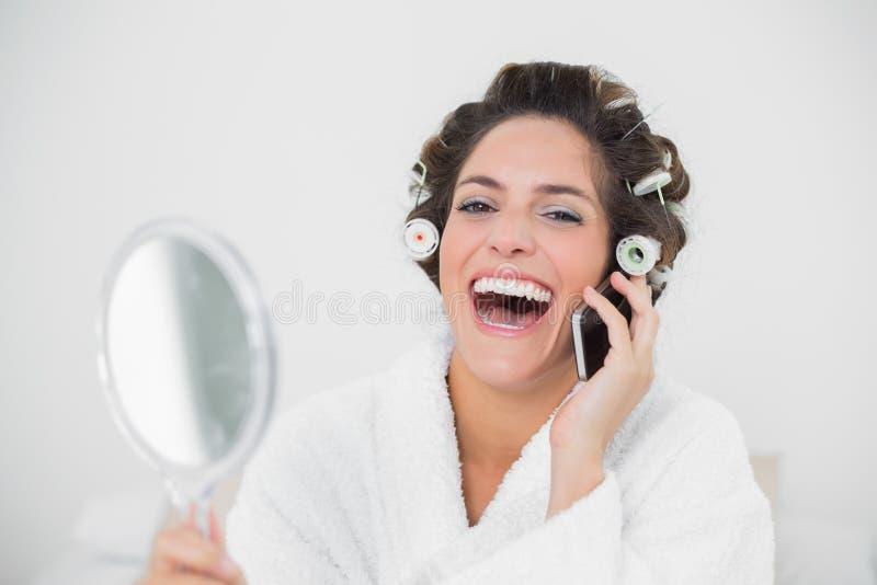 Castana naturale di risata facendo uso del telefono fotografia stock