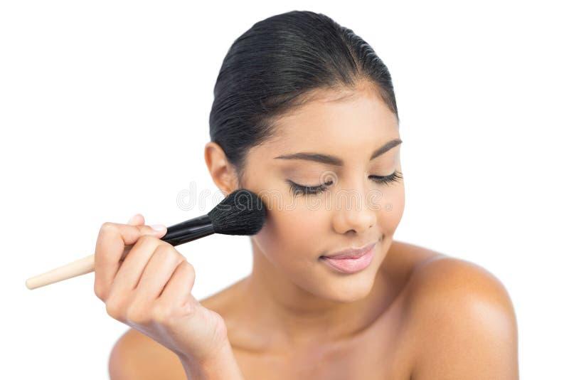Castana nudo contento facendo uso della spazzola della polvere con gli occhi chiusi fotografia stock libera da diritti
