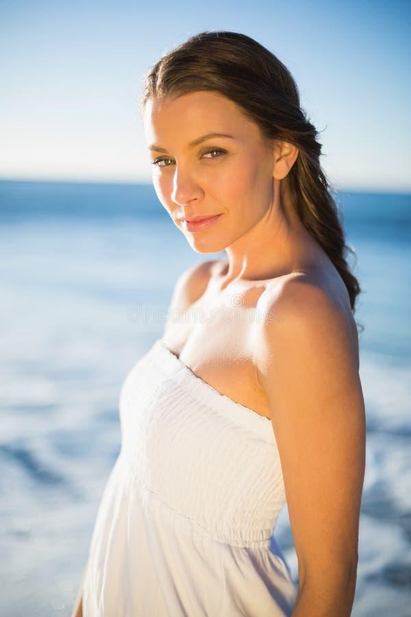 Castana pacifico nella posa bianca del vestito da estate fotografia stock