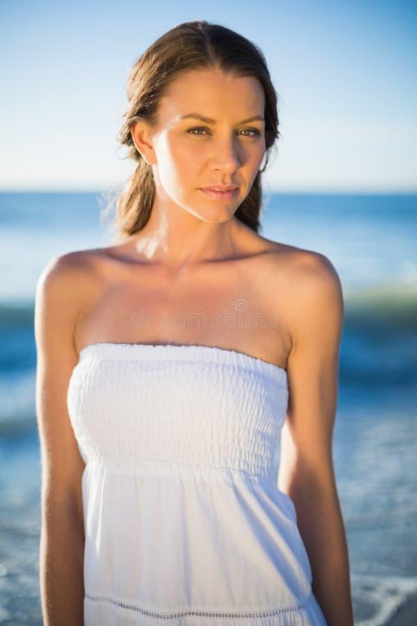 Castana serio nella posa bianca del vestito da estate fotografia stock libera da diritti