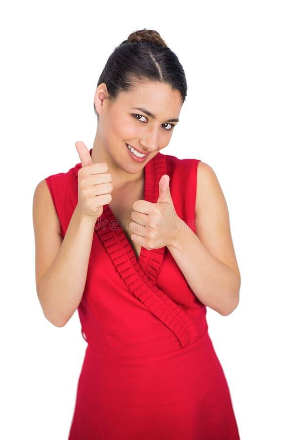Castana sexy allegro in pollici rossi del vestito su immagini stock libere da diritti
