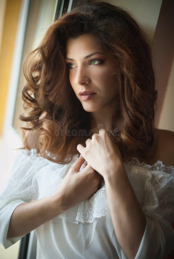 Castana sexy attraente in blusa bianca che posa provocatorio nella struttura della finestra Ritratto della donna sensuale nella s immagini stock