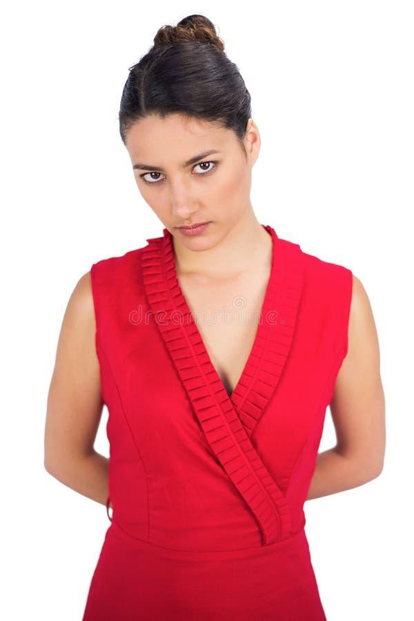 Castana sexy serio nella posa rossa del vestito fotografia stock libera da diritti