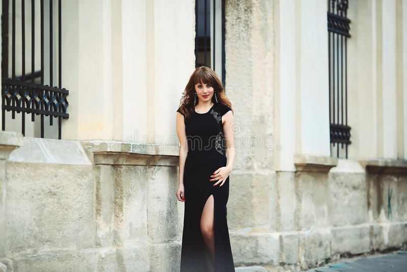 Castana sexy in vestito che sta vicino ad una parete bianca immagini stock