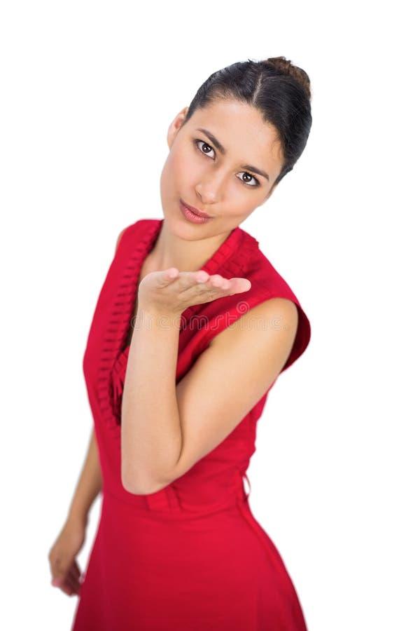 Castana sexy in vestito rosso che bacia alla macchina fotografica fotografie stock libere da diritti