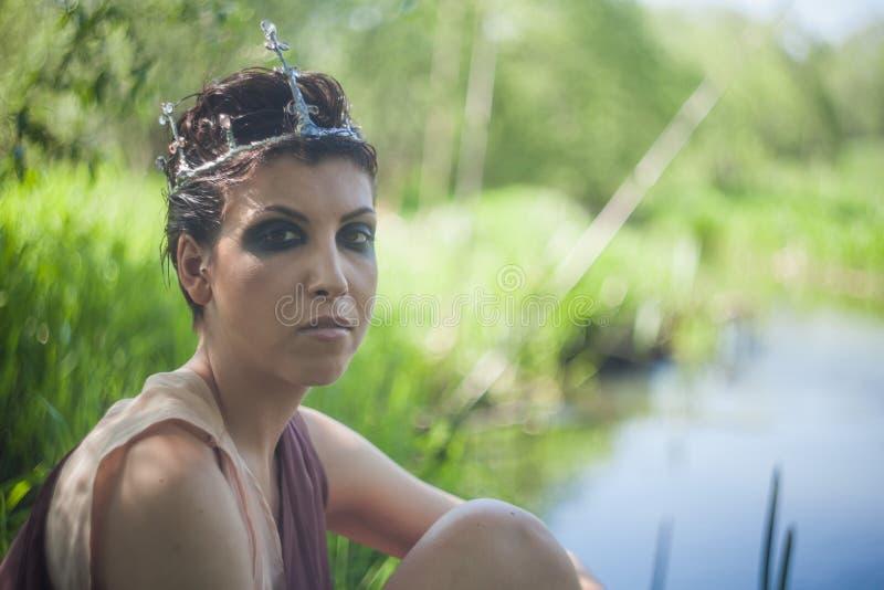 Castana snello in un vestito marrone con una corona sulla sua testa si siede sulla riva di uno stagno della foresta immagini stock libere da diritti