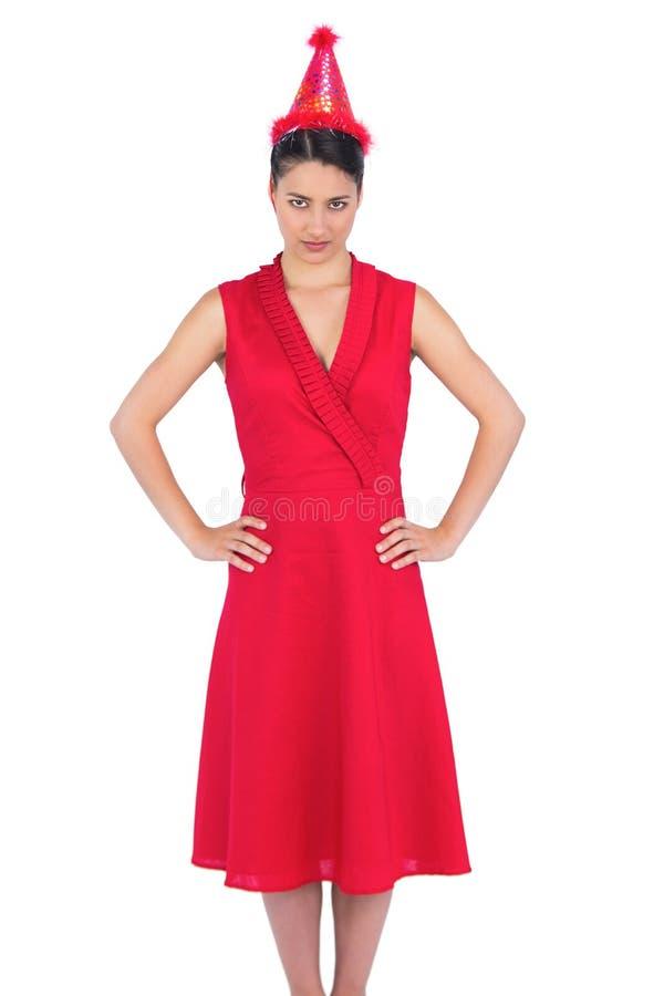 Castana splendido serio in cappello d'uso del partito del vestito rosso fotografia stock