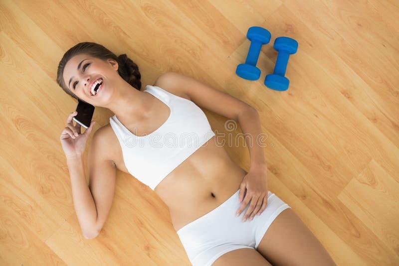 Castana sportivo allegro facendo uso di un telefono cellulare e trovarsi accanto alle teste di legno immagine stock