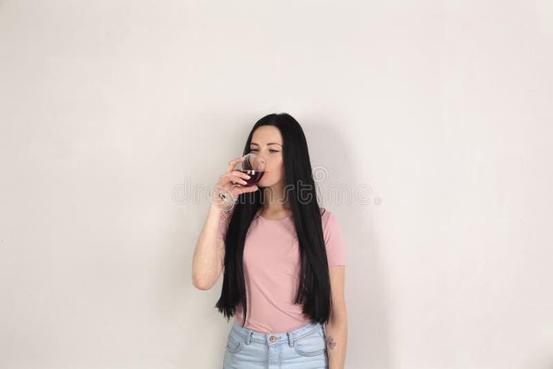 Castana sveglio con capelli lunghi beve il vino rosso, lei sta nel profilo contro i precedenti grigi immagine stock libera da diritti