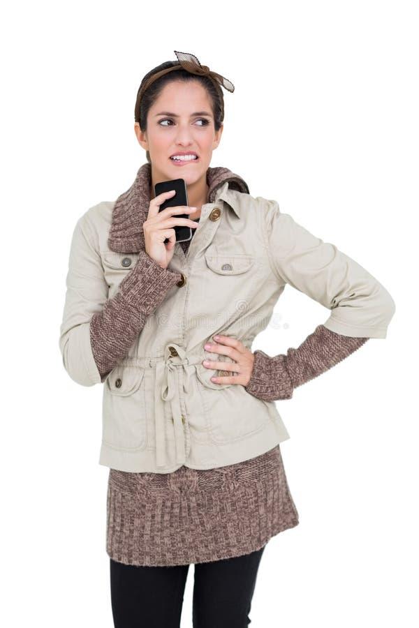 Castana sveglio pensieroso in smartphone della tenuta di modo di inverno immagini stock