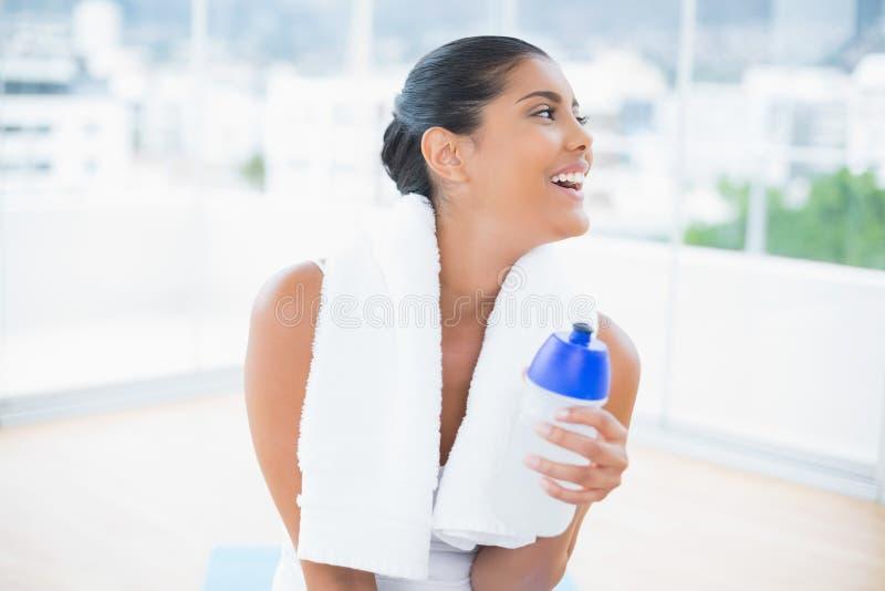 Castana tonificato allegro con la tenuta dell'asciugamano mette in mostra la bottiglia immagini stock