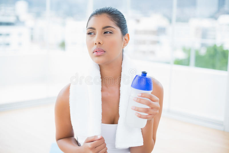 Castana tonificato serio con la tenuta dell'asciugamano mette in mostra la bottiglia immagine stock libera da diritti