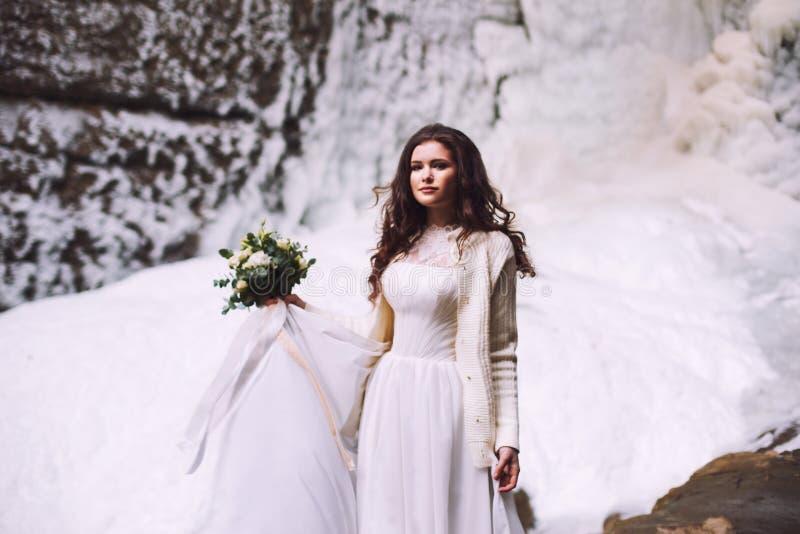 Castana in un vestito da sposa contro un fondo di un ghiacciaio nelle montagne immagini stock libere da diritti