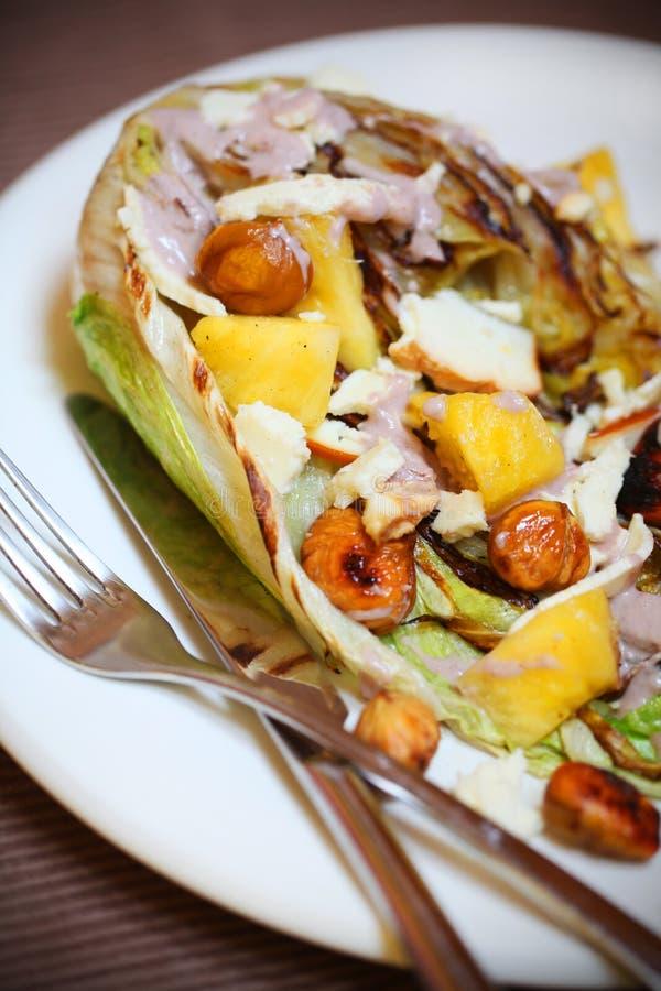 Castanha com salada grelhada, abacaxi, chicória e queijo de cabra fumado imagens de stock royalty free