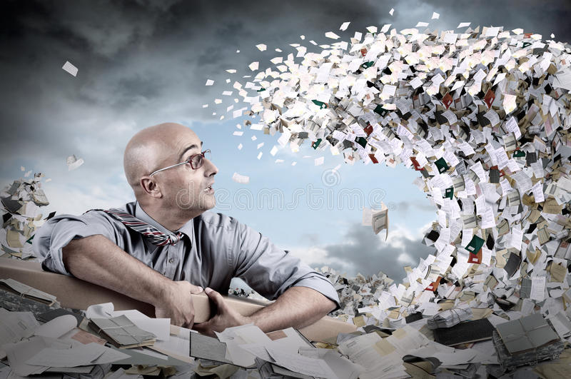 Castaway in bureaucracy. Castaway businessman in a sea of papers and files stock photo