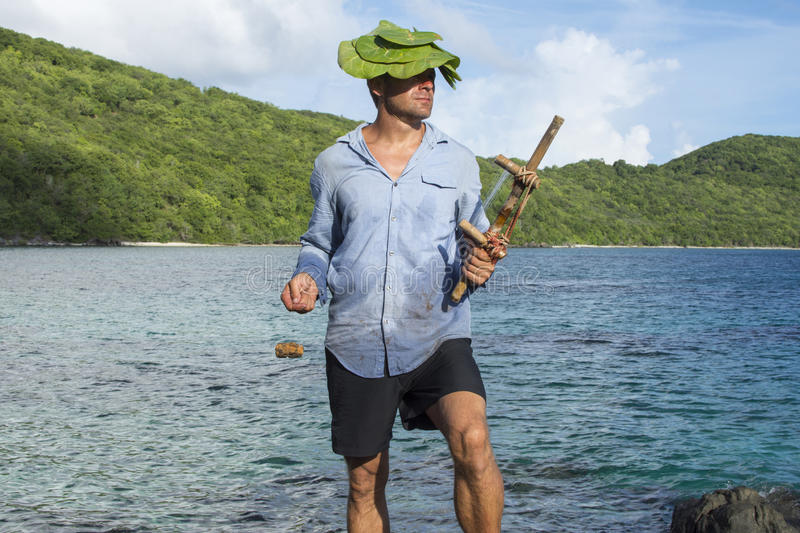 Castaway on deserted island. Caucasian male castaway wearing dirty wet clothes and sea grapes hat holds wooden fishing tool while gazing toward the sun on stock images