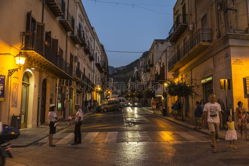 Street at night in Castellammare del Golfo, Sicily, Italy. Castellammare del Golfo, Italy - August 6, 2017: Street of the old town with people walking and police stock image